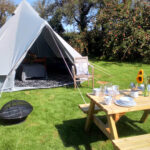 Outside Bell Tent with picnic table and fire pit